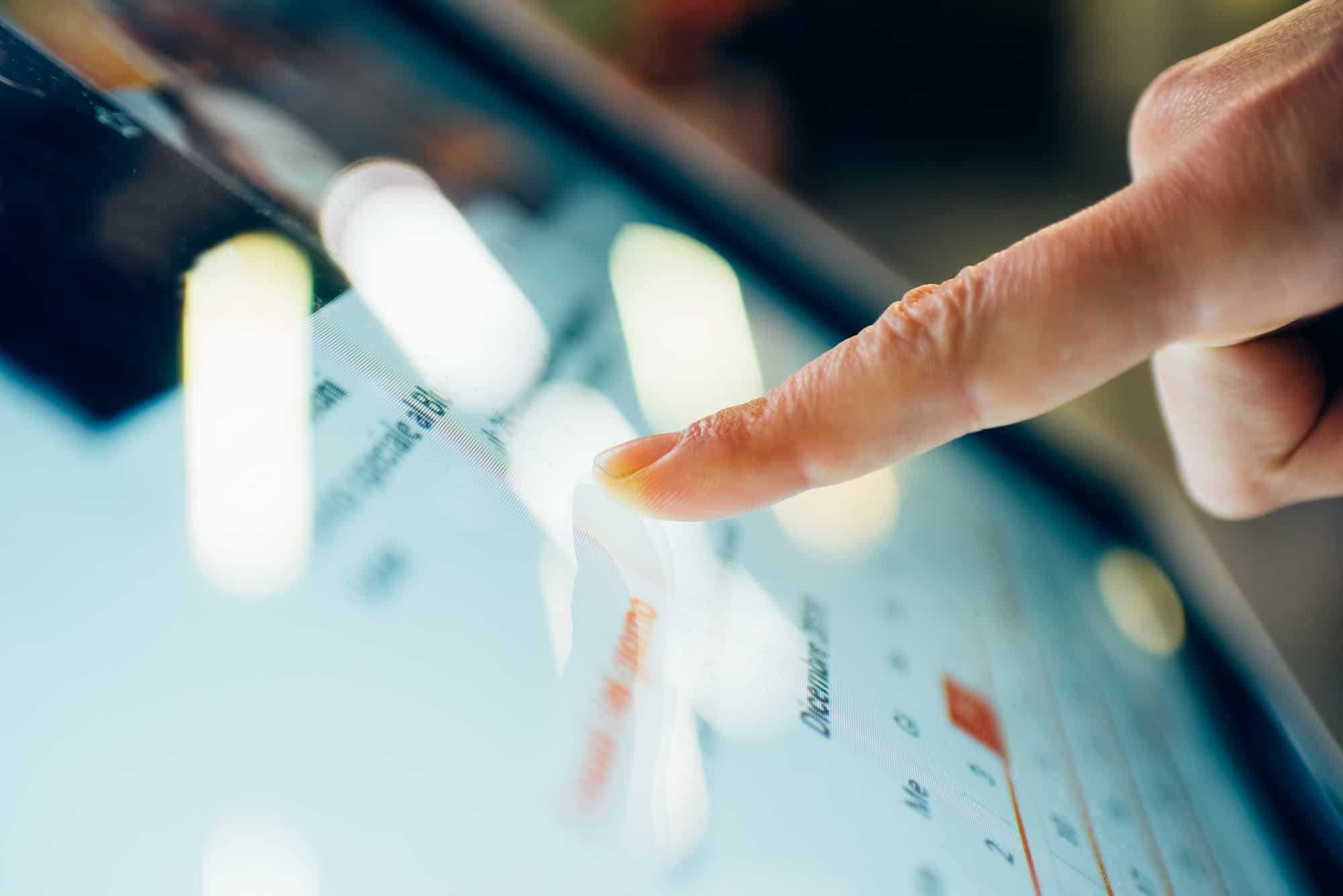 Close up on a finger touching the screen of a tablet - technolog